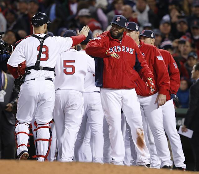 Boston Red Sox catcher David Ross (3) and David Ortiz, right, celebrate with teammates after the Red Sox defeated the St. Louis Cardinals, 8-1, in Game 1 of baseball's World Series Wednesday, Oct. 23, 2013, in Boston. (AP Photo/Elise Amendola)