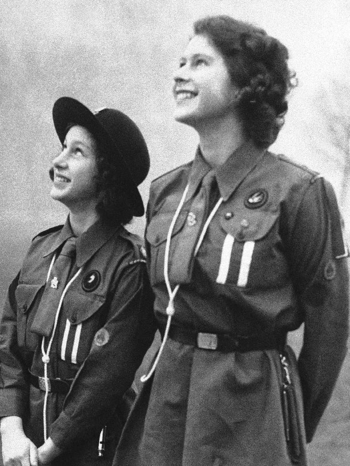 "FILE - This is a Feb. 20, 1943 file photo of Britain's Princess Elizabeth, right, and her sister, Princess Margaret as they  watch their carrier pigeon circle in the sky after they have released it with a message for Lady Baden-Powell.  It was one of the many messages sent by Girl Guides throughout Britain on Thinking Day which marks the Birthday late Lord Baden-Powell, founder of the Scout movement.  Britain's Girl Guides have dropped a reference to God in their pledge. Gone is the reference to loving God, replaced by a call to ""be true to myself and develop my beliefs."" The new pledge unveiled Wednesday  June 19, 2013, does retain a reference to serving the queen. (AP Photo, File)"