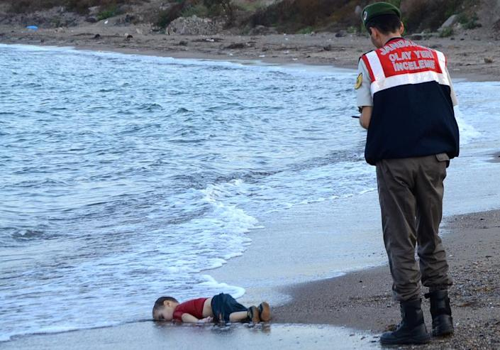A Turkish police officer stands next to the body of Aylan Kurdi in September 2015 (AFP Photo/Nilufer Demir)