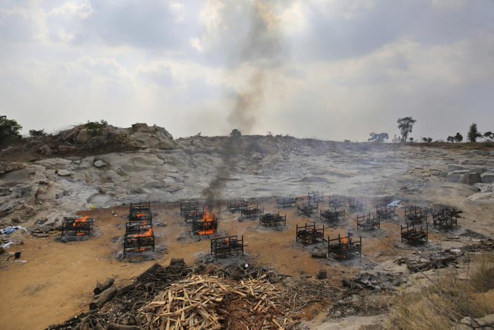 Funeral pyres of twenty-five COVID-19 victims burn at an open crematorium set up at a granite quarry on the outskirts of Bengaluru, India, Wednesday, May 5, 2021. (AP Photo/Aijaz Rahi)