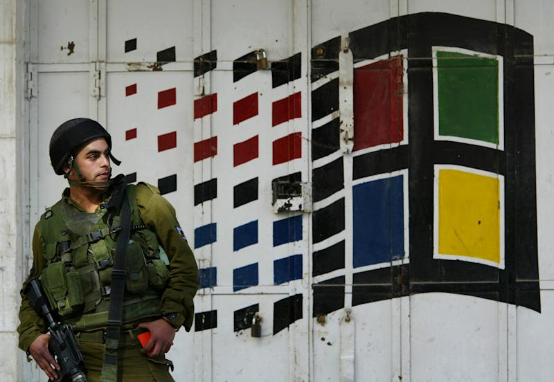 "FILE - In this Friday, Feb. 7, 2003 file photo, an Israeli soldier stands in front of a closed computer store as he conducts document checks of Palestinians in the southern West Bank town of Hebron. The Israeli military told the media Tuesday, Oct. 19, 2010, that is banning soldiers from using social media sites in an attempt to prevent security leaks and embarrassing videos going viral. The measure is aimed at preventing sensitive information from reaching its ""enemies"" via Facebook, Twitter and other popular sites. (AP Photo/Lefteris Pitarakis, File)"