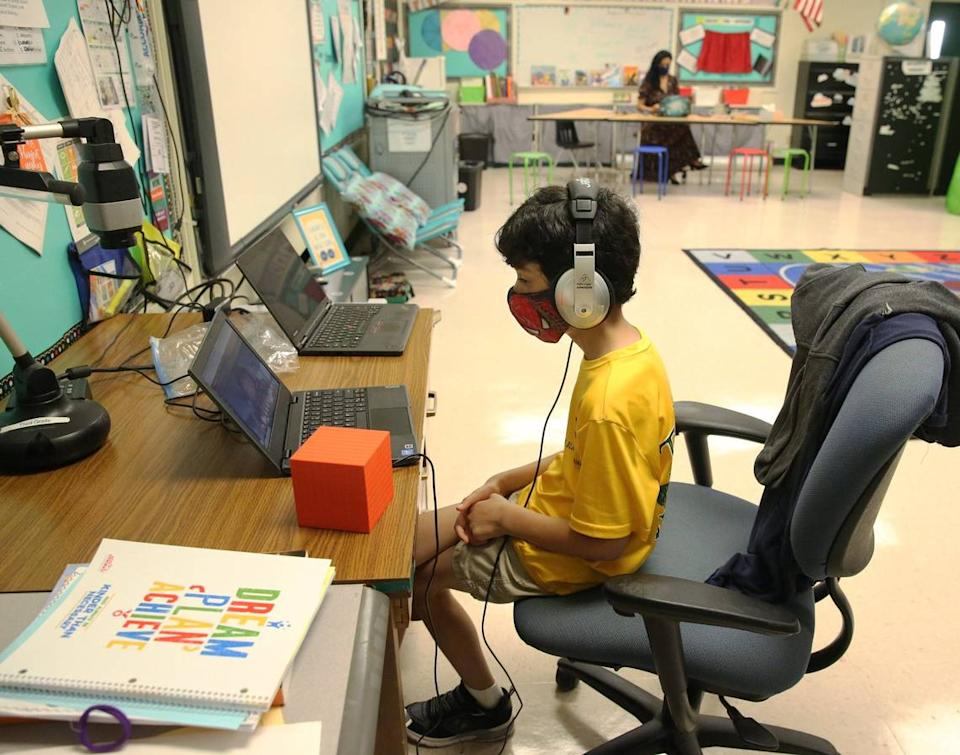 Nova Blanche Forman Elementary School teacher Attiya Batool teaches her fourth grade class virtually as her son, Nabeel, does his second grade classwork online wearing a mask and headphones during the first day of school in Broward, Wednesday, August 19, 2020. All classes in Broward public schools are being taught remotely. The school district has made some adjustments where teachers may bring their child to their classroom to do remote learning while they teach.