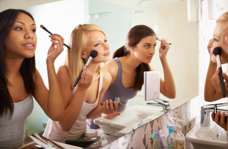 Three women looking in the mirror while applying makeup