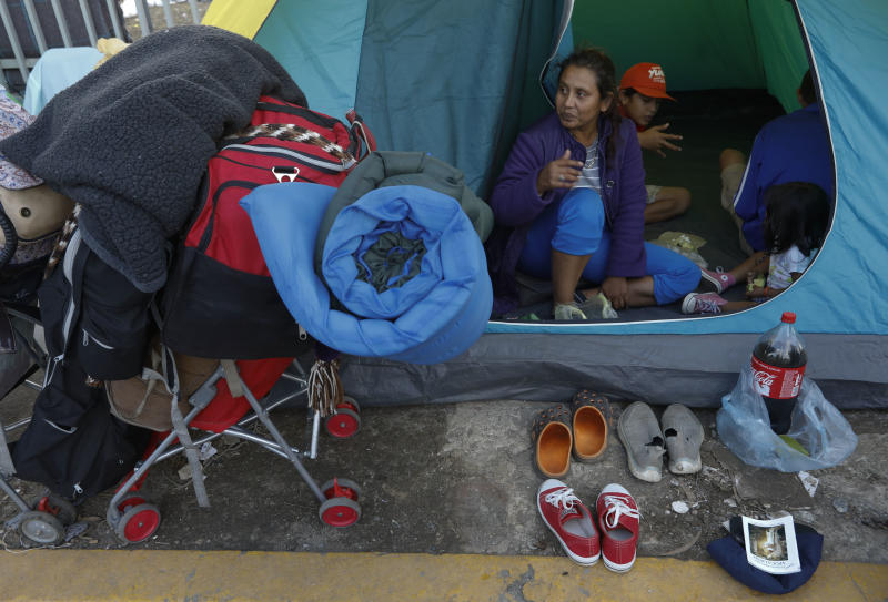 A migrant family with their belongings packed waits in their tent on the street for buses to arrive to carry them to a new shelter in Tijuana Mexico Saturday Dec. 1 2018. By Saturday afternoon most of the thousands of migrants who had been camped
