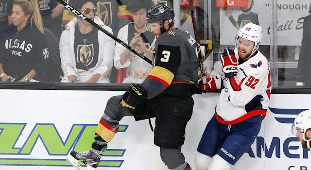 Washington Capitals center Evgeny Kuznetsov, right, of Russia, winces as he is checked by Vegas Golden Knights defenseman Brayden McNabb. (AP Photo/Ross D. Franklin)