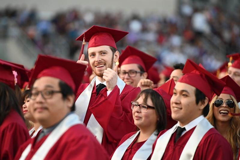 """Students earning degrees at Pasadena City College participate in the graduation ceremony, June 14, 2019, in Pasadena, California. - With 45 million borrowers owing $1.5 trillion, the student debt crisis in the United States has exploded in recent years and has become a key electoral issue in the run-up to the 2020 presidential elections. """"Somebody who graduates from a public university this year is expected to have over $35,000 in student loan debt on average,"""" said Cody Hounanian, program director of Student Debt Crisis, a California NGO that assists students and is fighting for reforms. (Photo by Robyn Beck / AFP) (Photo credit should read ROBYN BECK/AFP via Getty Images)"""