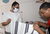 Tunisian fashion designer Chems Eddine Mechri, left, works in his studio in Oued Elil, 25 kilometres (15 miles) from Tunis, Saturday, Oct. 3, 2020. The fusion of high-quality, locally sourced materials, traditional Tunisian craftsmanship and ecological, ethical fashion practices are central to Mechri's vision, who founded his women's fashion label Née in 2019. (AP Photo/Hassene Dridi)