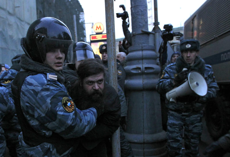 Russian police officers detain an opposition protester during a protest near the Central Election Committee in Moscow, Monday, March, 5, 2012. Demonstrators are contesting the outcome of Russia's presidential election, pointing to a campaign heavily slanted in Putin's favor and to reports of widespread violations in Sunday's ballot. (AP Photo/Sergey Ponomarev)