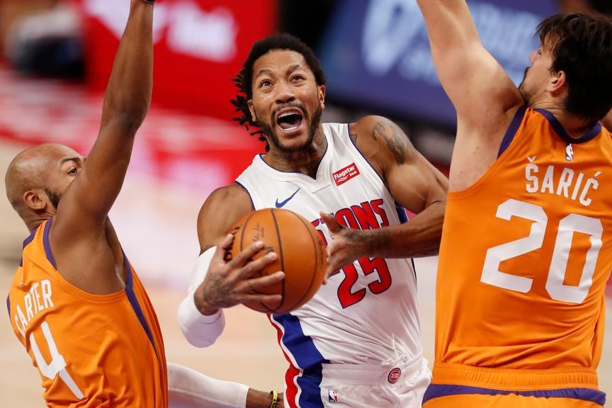 Derrick Rose slices through defenders on way to the basket in Pistons white uniform