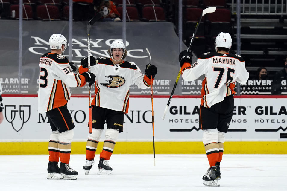 Anaheim Ducks defenseman Josh Mahura (76) celebrates with center Trevor Zegras (46) and right wing Jakob Silfverberg (33) after scoring a goal during the second period of the team's NHL hockey game against the Arizona Coyotes, Wednesday, Feb. 24, 2021, in Glendale, Ariz. (AP Photo/Rick Scuteri)