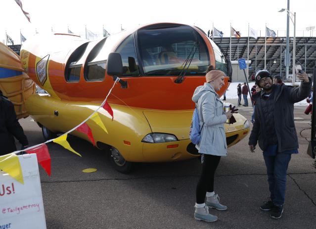 Mariano and Beth Velasco of Denver take a selfie with the Oscar Meyer weinermobile outside Falcon Stadium before an NHL Stadium Series hockey game Saturday, Feb. 15, 2020, at Air Force Academy, Colo. The Colorado Avalanche host the Los Angeles Kings in the contest. (AP Photo/David Zalubowski)