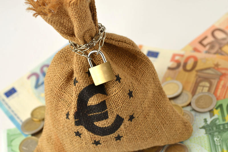 Close-Up Of Sack Locked By Chain And Pad Lock With Euro Symbol On Currency