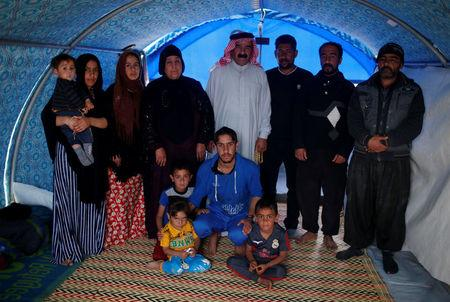 Displaced Iraqi Meshal Hadi (C), 65, poses for a photograph with his family inside their tent at Hammam al-Alil camp south of Mosul, Iraq, April 1, 2017. Hadi, a well-off businessman in his former life, said the family had to flee because of the shelling and the lack of water and electricity. He has no idea if his Mosul house is still standing; he lost contact with friends and neighbours. During the day, women keep the tent clean while men look for food. The family wants to go back home as soon as possible. REUTERS/Suhaib Salem