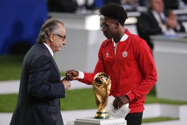 Decio de Maria, President of the Football Association of Mexico, left, and Canadian soccer player Alphonso Davies, right, present a joint United bid by Canada, Mexico and the United States to host the 2026 World Cup at the FIFA congress in Moscow, Russia, Wednesday, June 13, 2018. (AP Photo/Pavel Golovkin)