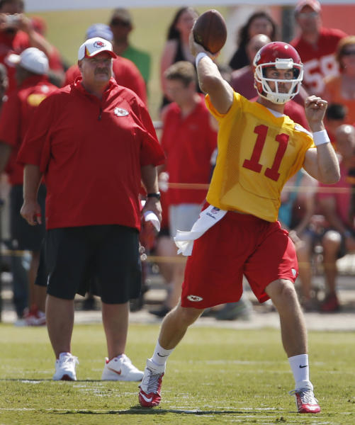 Kansas City Chiefs coach Andy Reid, left, stands behind quarterback Alex Smith (11) during NFL football training camp in St. Joseph, Mo., Friday, July 26, 2013. (AP Photo/Orlin Wagner)