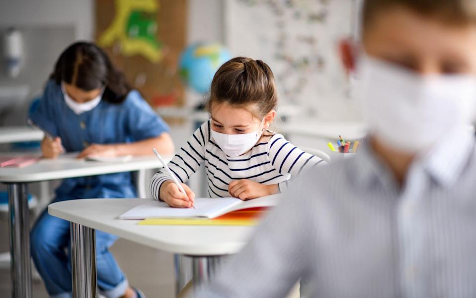 A child works at school in a face mask - Halfpoint