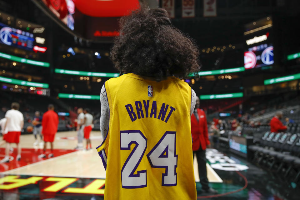 A fan watches warmups while wearing a Kobe Bryant jersey after news reports of his death in a helicopter crash prior to an NBA basketball game between the Washington Wizards and the Atlanta Hawks, Sunday, Jan. 26, 2020, in Atlanta. (AP Photo/Todd Kirkland)