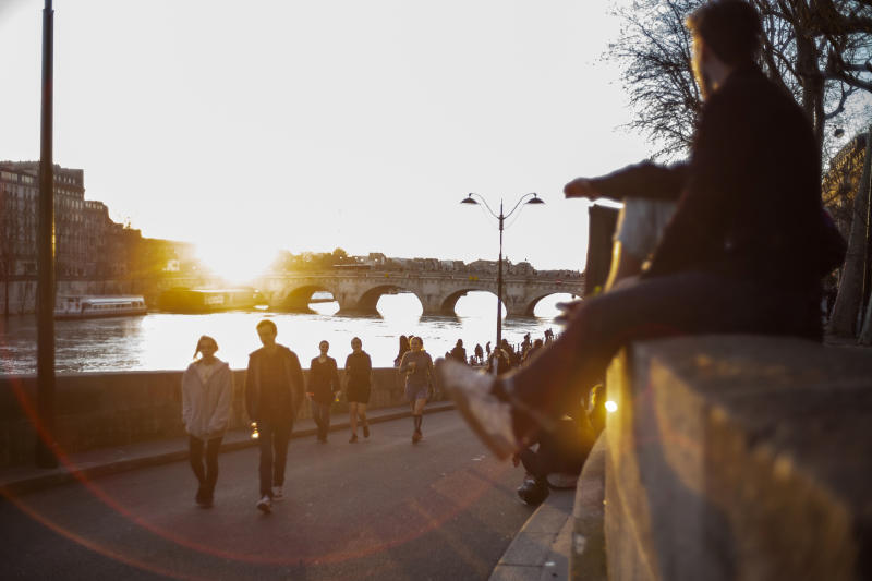 People stroll along the Seine river banks at sunset Sunday March 15, 2020 in Paris. For most people, the new coronavirus causes only mild or moderate symptoms. For some it can cause more severe illness. (AP Photo/Rafael Yaghobzadeh)