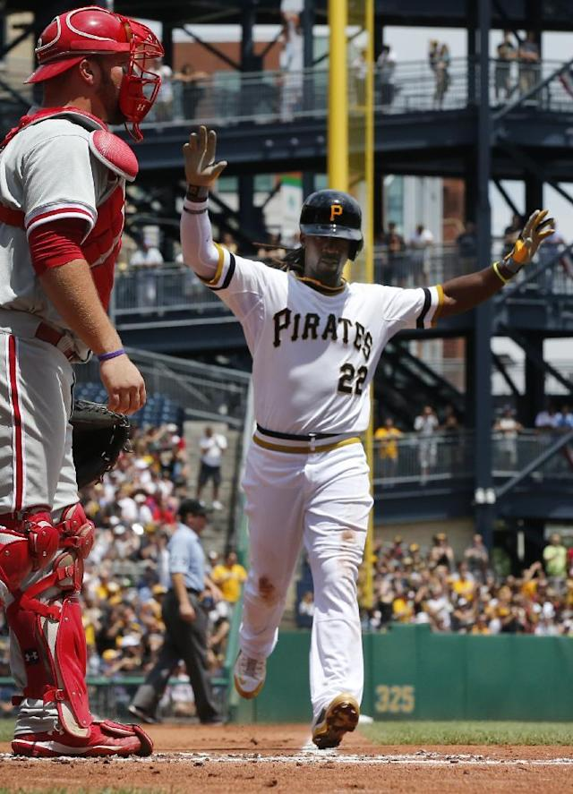 Pittsburgh Pirates' Andrew McCutchen,right, scores on a double by Pirates' Russell Martin off Philadelphia Phillies starting pitcher A.J. Burnett in the first inning of a baseball game against the Pittsburgh Pirates in Pittsburgh Sunday, July 6, 2014. At left is Philadelphia Phillies catcher Cameron Rupp. (AP Photo/Gene J. Puskar)