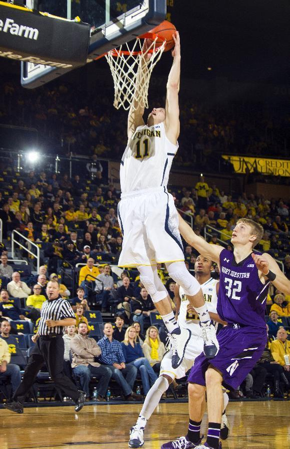 Michigan guard Nik Stauskas (11) dunks the ball while trailed by Northwestern forward Nathan Taphorn (32) in the first half of an NCAA college basketball game at Crisler Center in Ann Arbor, Mich., Sunday, Jan. 5, 2014. (AP Photo/Tony Ding)