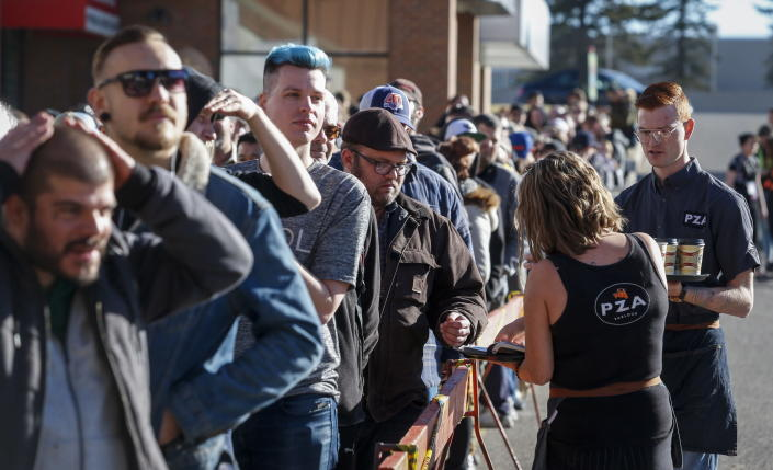 <p>Cafe employees offer coffee to people lining-up to purchase legal cannabis in Calgary, Alberta, Wednesday, Oct. 17, 2018. (Photo: Jeff McIntosh/The Canadian Press via AP) </p>