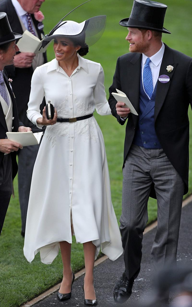 The Duchess of Sussex wears a Givenchy shirt dress and Philip Treacy hat at Royal Ascot - AFP