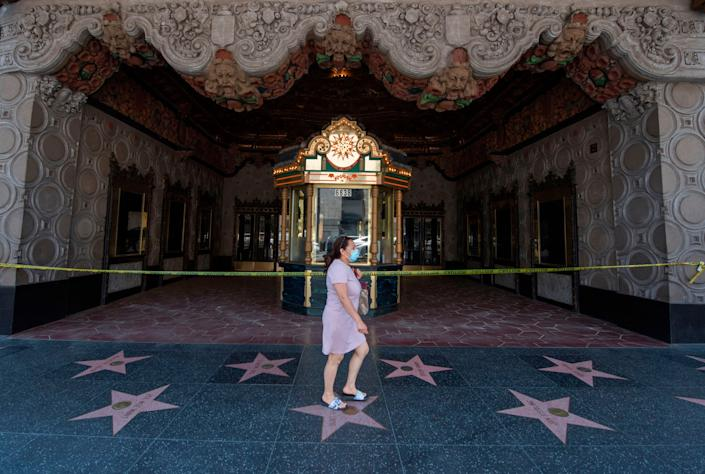 A woman walks past the El Capitan Theater on Hollywood Boulevard in Los Angeles on June 12, 2020. As coronavirus cases in California hit a record high this week, the state is rolling back reopening plans. (Photo: MARK RALSTON via Getty Images)