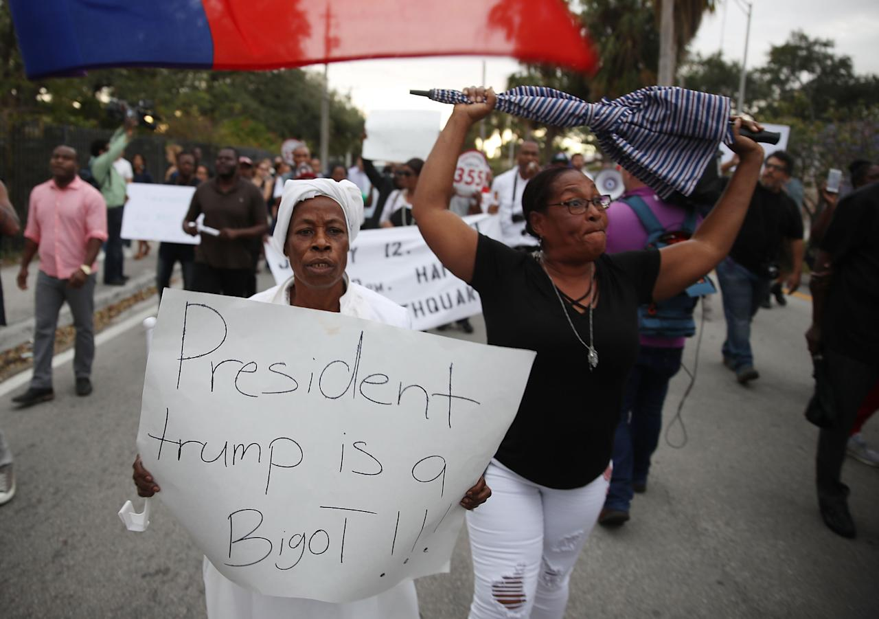 <p>Jocelyne Pierre and Yanick Gorneo (L-R) join with others to mark the 8th anniversary of the massive earthquake in Haiti and to condemn President Donald Trump's reported statement about immigrants from Haiti, Africa and El Salvador on Jan. 12, 2018 in Miami, Fla. (Photo: Joe Raedle/Getty Images) </p>