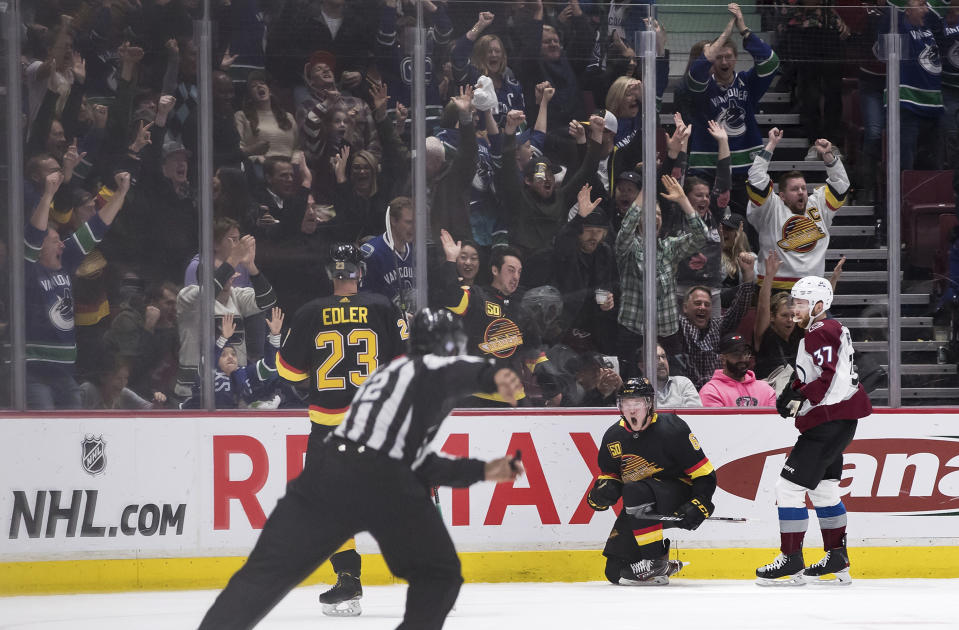 Vancouver Canucks' Brock Boeser, second from right, and Alexander Edler (23), of Sweden, celebrate Boeser's tying goal, as Colorado Avalanche's J.T. Compher, right, watches during the third period of an NHL hockey game Saturday, Nov. 16, 2019, in Vancouver, British Columbia. (Darryl Dyck/The Canadian Press via AP)