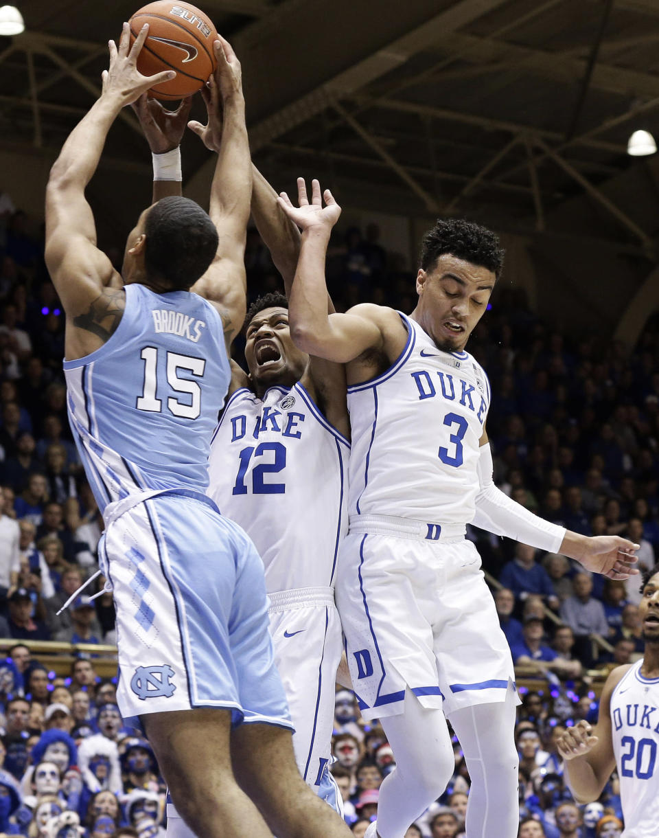 Duke's Javin DeLaurier (12) and Tre Jones (3) guard North Carolina's Garrison Brooks (15) during the first half of an NCAA college basketball game in Durham, N.C., Wednesday, Feb. 20, 2019. (AP Photo/Gerry Broome)