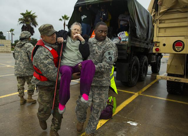 <p>Texas Army National Guard members Sergio Esquivel, left, and Ernest Barmore carry 81-year-old Ramona Bennett after she and other residents were rescued from their Pine Forest Village neighborhood due to high water from Hurricane Harvey August 29, 2017 in Houston, Texas. Harvey, which made landfall north of Corpus Christi late Friday evening, is expected to dump upwards to 40 inches of rain in areas of Texas over the next couple of days. (Photo: Erich Schlegel/Getty Images) </p>
