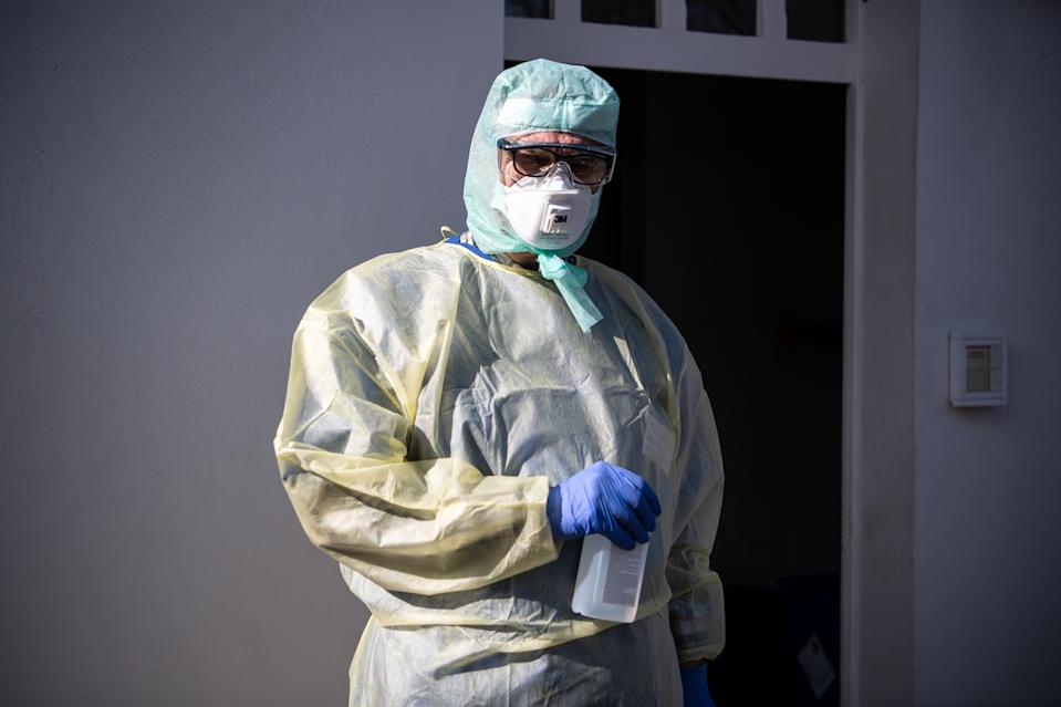16 March 2020, Bremen: An employee from the Klinikum Bremen-Ost stands in protective clothing in front of the new corona outpatient clinic and receives patients. Photo: Sina Schuldt/dpa (Photo by Sina Schuldt/picture alliance via Getty Images)