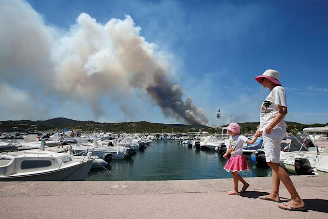 <p>A woman and her daughter walk near leisure boats in a port as a plume of smoke from burning fires fills the sky in Bormes-les-Mimosas, in the Var department, France, July 26, 2017. (Jean-Paul Pelissier/Reuters) </p>