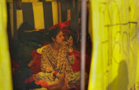 A newly wed woman looks in a mirror as she joins her farmer husband for a protest in a makeshift tent in one of the three main protest sites outside New Delhi's border, India, Friday, Feb. 5, 2021. India's agriculture minister on Friday defended the new agriculture reform laws in Parliament, dampening hopes of any quick settlement with tens of thousands of protesting farmers demanding their repeal by blocking three highways connecting New Delhi to northern India for over two months now. (AP Photo/Manish Swarup)