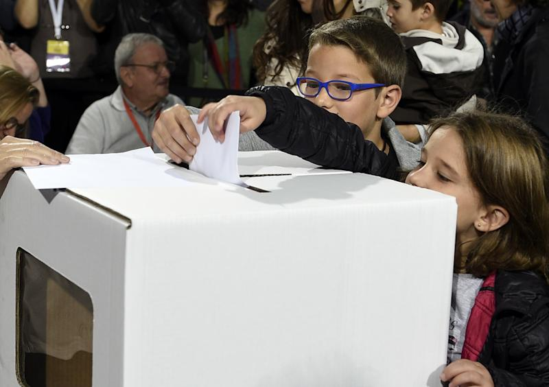 Two children place the ballot of their mother in the ballot box on November 9, 2014, in Barcelona during the symbolic vote on independence for Catalonia from Spain (AFP Photo/Lluis Gene)
