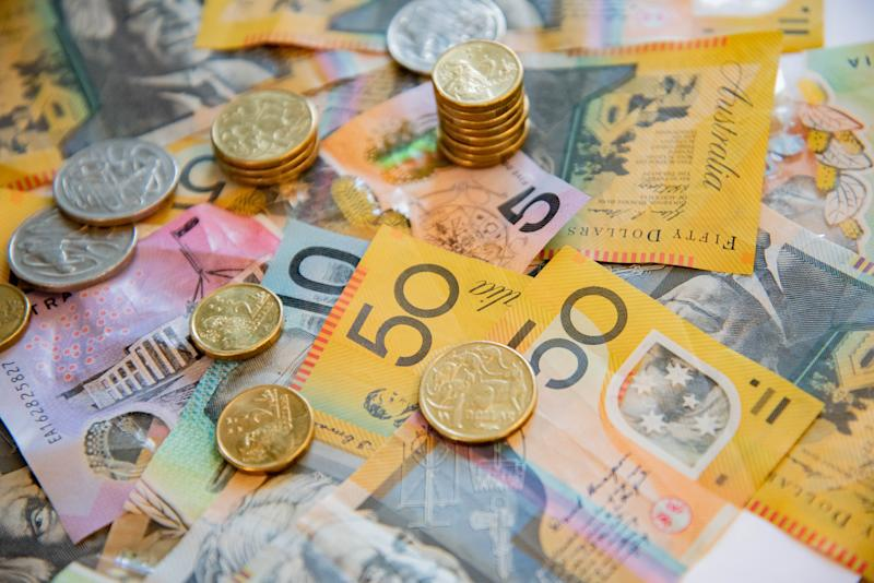 Australian notes and coins spilled out on a table.