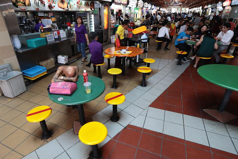 Chairs are marked with red tape at a hawker centre in Singapore as authorities implement social distancing measures to combat the coronavirus on 19 March, 2020. in Singapore. (PHOTO: Getty Images)