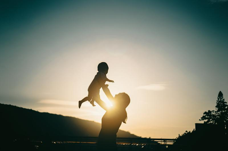 Silhouette of mother raising baby girl in the air outdoors against sky during a beautiful sunset