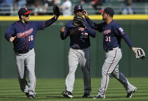 Minnesota Twins outfielders Josh Willingham (16), Aaron Hicks (32), and Oswaldo Arcia (31), celebrate after defeating the Chicago White Sox 5-3 in a baseball game in Chicago, April 21, 2013. (AP Photo/Paul Beaty)