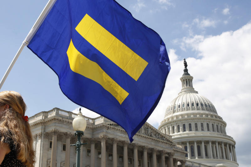 """FILE - In this July 26, 2017, file photo, a supporter of LGBT rights holds up an """"equality flag"""" on Capitol Hill in Washington, during an event held by Rep. Joe Kennedy, D-Mass. in support of transgender members of the military. The Trump administration is asking the Supreme Court to fast-track cases on the president's decision to prevent certain transgender people from serving in the military. The administration asked the court on Nov. 23, 2018, to take up three cases on the issue. (AP Photo/Jacquelyn Martin, File)"""