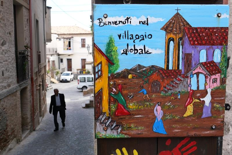 The colourful welcoming signs for refugees are still up, but the town of Riace has swung far-right, against the migrant experiment it once championed (AFP Photo/Alberto PIZZOLI)