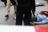 EDITORS NOTE: Graphic content / Policemen gather around the body of an alleged gunman outside the Pakistan Stock Exchange building in Karachi on June 29, 2020. - Gunmen attacked the Pakistan Stock Exchange in Karachi on June 29, with four of the assailants killed, police said. (Photo by Asif HASSAN / AFP) (Photo by ASIF HASSAN/AFP via Getty Images)
