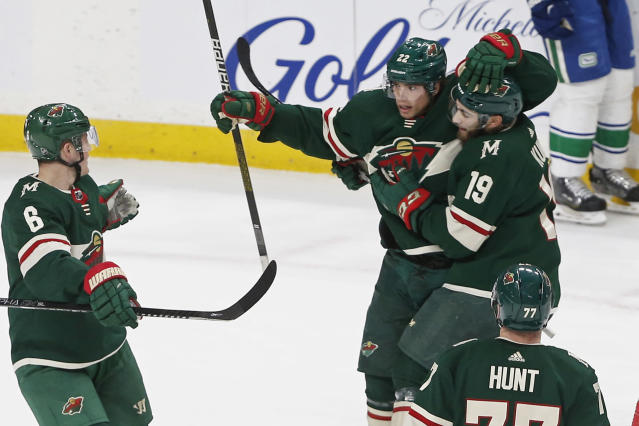 Minnesota Wild's Kevin Fiala, top left, is congratulated by teammates after his power-play goal against the Vancouver Canucks during the first period of an NHL hockey game Thursday, Feb. 6, 2020, in St. Paul, Minn. (AP Photo/Jim Mone)