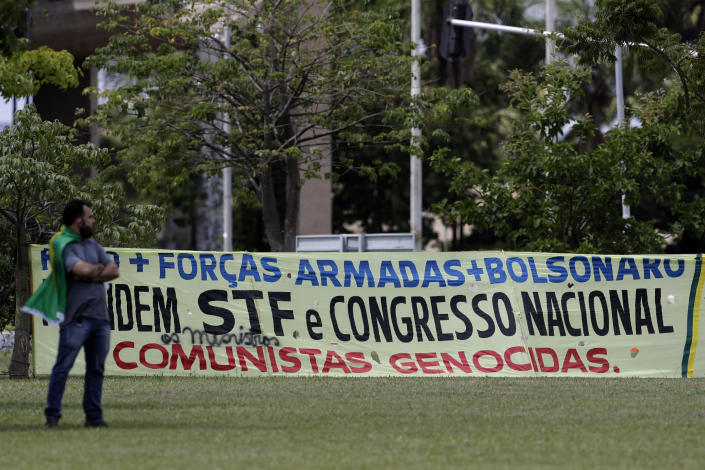 """A supporter of Brazilian President Jair Bolsonaro wearing a national flag as a cape, stands next to a banner with a message that reads in Portuguese: """"Armed Forces + Bolsonaro. Arrest Supreme Court and Congress. Genocidal Communists,"""" during a gathering to commemorate the 1964 military coup that established a decades-long dictatorship, in the Ministries Esplanade in Brasilia, Brazil, Wednesday, March 31, 2021. The leaders of all three branches of Brazil's armed forces jointly resigned on Tuesday following Bolsonaro's replacement of the defense minister, causing widespread apprehension of a military shakeup to serve the president's political interests. (AP Photo/Eraldo Peres)"""