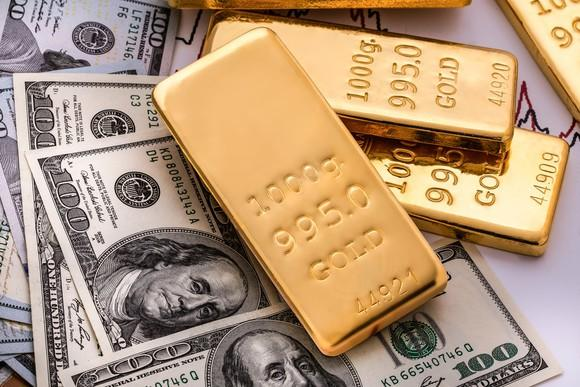 Gold bars on top of a pile of $100 bills.