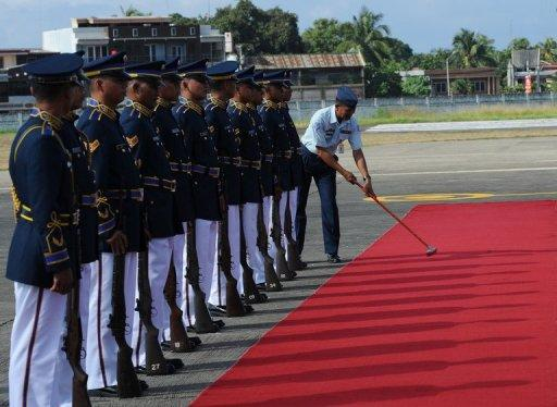 A Philippine airforce soldier cleans a red carpet in front of an honor guard on July 5