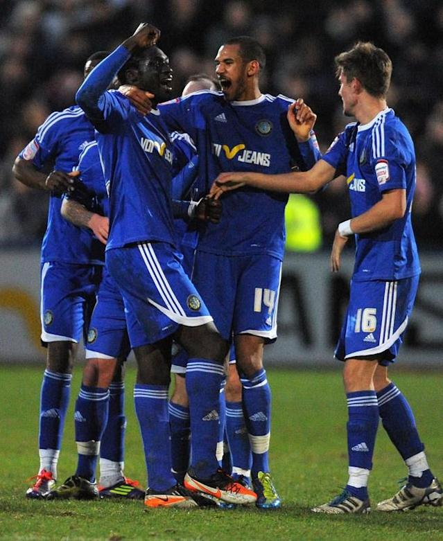 "Macclesfield Town's Guinean midfielder Arnaud Mendy (3rd R) celebrates after scoring on January 7 2012 during the FA Cup football match against Bolton Wanderers at Moss Rose,Macclesfield, northwest England. RESTRICTED TO EDITORIAL USE. No use with unauthorized audio, video, data, fixture lists, club/league logos or ""live"" services. Online in-match use limited to 45 images, no video emulation. No use in betting, games or single club/league/player publications. (Photo by Andrew Yates/AFP/Getty Images)"