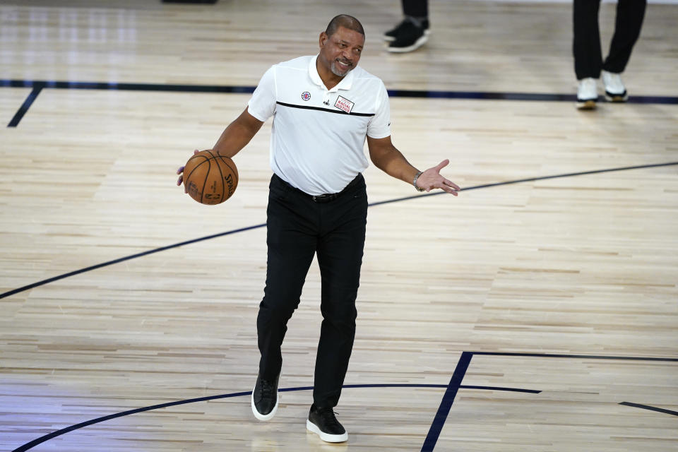 Doc Rivers with a ball in his hands on the basketball court at Disney.