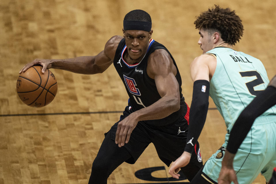 Los Angeles Clippers guard Rajon Rondo (4) brings the ball up court while guarded by Charlotte Hornets guard LaMelo Ball (2) during the first half of an NBA basketball game in Charlotte, N.C., Thursday, May 13, 2021. (AP Photo/Jacob Kupferman)