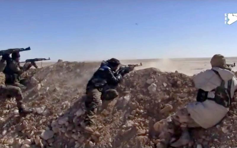 Fighters from the SDF opening fire on an Islamic State group's position, in Raqqa's eastern countryside, Syria. - Credit: AP